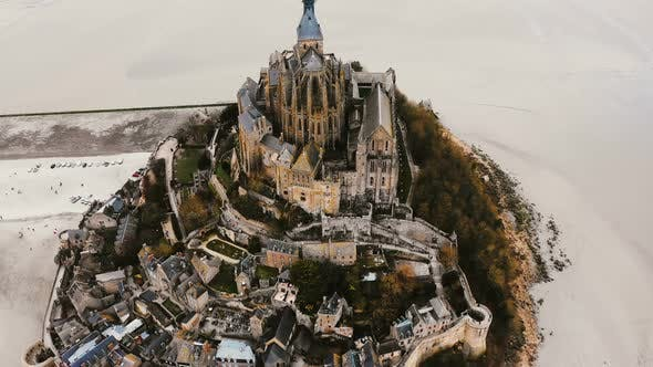 Cover Image for Drone Rises, Tilts Down on Mont Saint Michel, Ancient Island Fortress Town During Low Tide, World