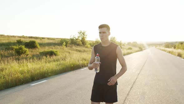 Sportsman Walking on Road at Nature with Sunset and Drinking Water From Bottle