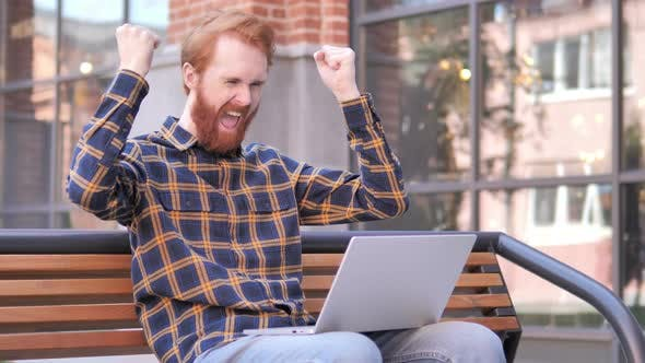 Thumbnail for Redhead Beard Young Man Celebrating on Laptop Sitting Outside Office