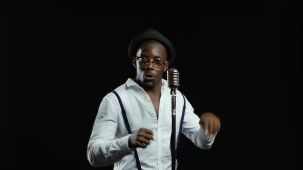 Man African American Singer Sings Into a Microphone and Dance. Black Background