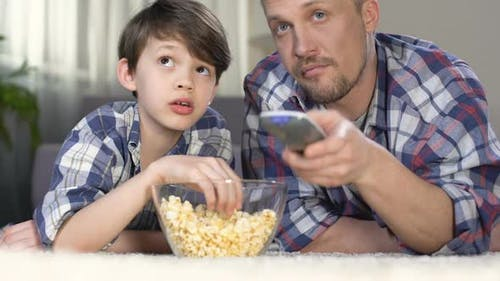 Male Company Spending Time Together Watching Tv and Eating Popcorn, Fatherhood