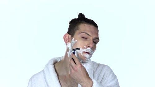 Man Shaves Stubble with Razor Blade. White Background. Slow Motion