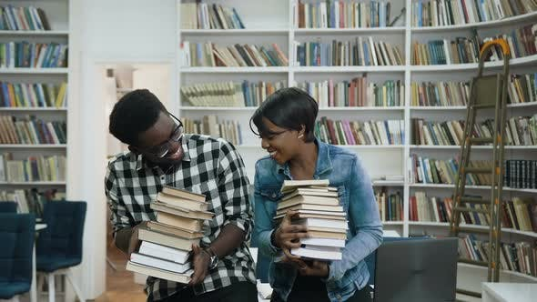 Thumbnail for Young African Couple Holding a Bunch of Books in the Hands