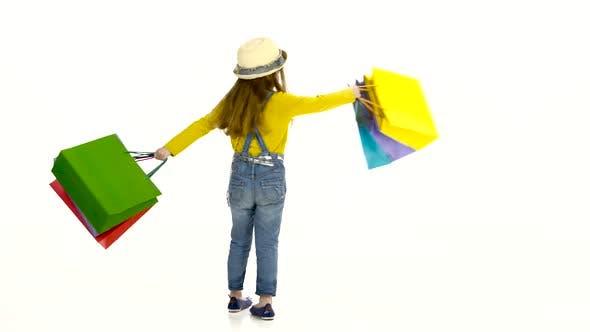 Thumbnail for Kleines Mädchen mit Paketen in Händen Wirbel um ihn. Weißer Hintergrund