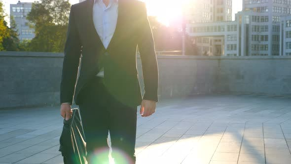 Young Businessman with a Briefcase Walking in City Street. Business Man Commuting To Work in the
