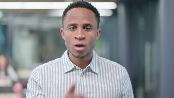 African Businessman with Finger on Lips Quiet Sign
