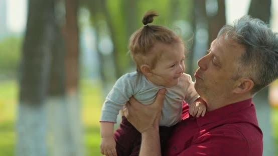 Der Mensch hält ein Baby in seinen Armen und küsst ihn, glückliche Vaterschaft. Papa verbringt Zeit mit dem Kind