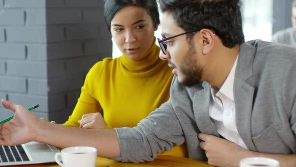 Cover Image for Coworkers Discussing Business Plan on Laptop at Cafe Table