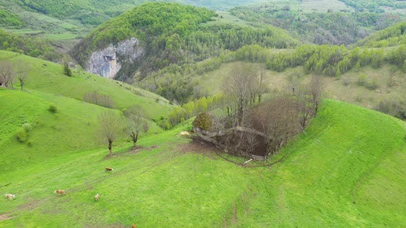 Aerial View of Spring Countryside Landscape with Wooden Houses and Limestone Cliffs