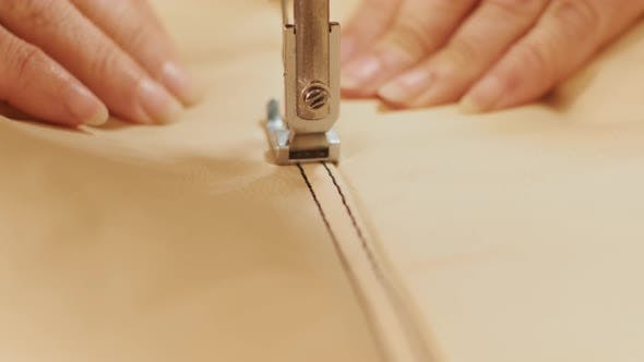 Closeup of sewing machine working part with leather. Sewing machine