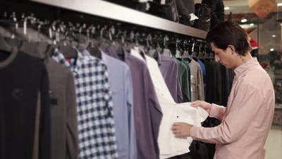 Male Shopper Is Choosing a Shirts in a Shop in a Shopping Mall