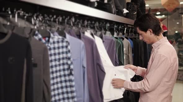 Male Shopper Is Choosing a Shirts in a Shop in a Shopping Mall