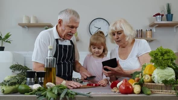 Thumbnail for Senior Grandparents Couple with Digital Tablet and Granddaughter Cutting Vegetables in Kitchen