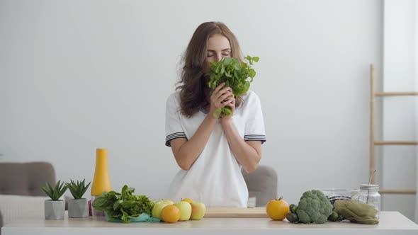 Thumbnail for Junge lächelnde Frau schnüffeln frische Grüns stehend am Tisch in moderne Küche