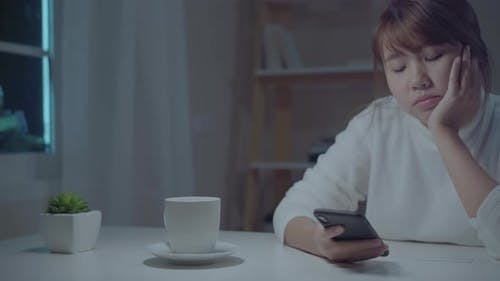 Young Asian woman using mobile phone at home. female insomnia bored and tired.