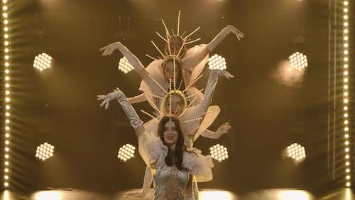 Young Women Dance in Sexy Tight Fitting Costumes and Original Crowns in Slow Motion. Neon Light