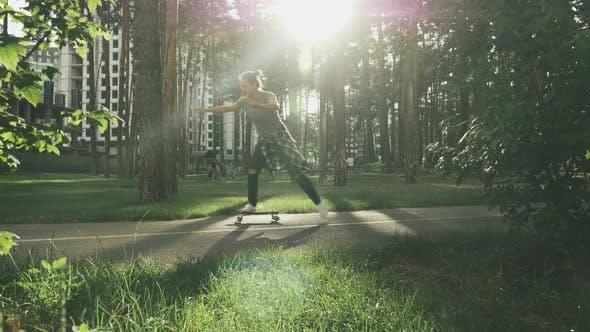 Thumbnail for Girl learning to skating on skateboard in park at sunset. Millennial female skateboarding