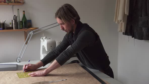 Thumbnail for Man Tailor Draws Clothing Pattern While Working in Workshop
