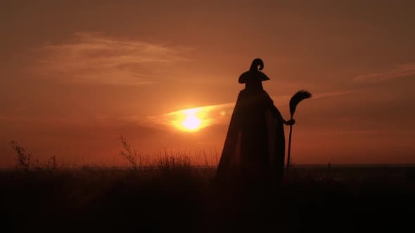 Thumbnail for Girl in Fancy Dress Witch Holds a Broom Looking on Sunrise Lens Flare