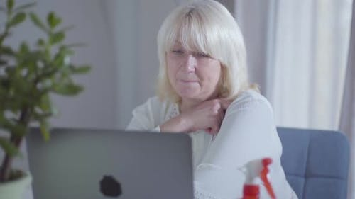 Senior Caucasian Woman Watching Movie on Laptop Screen and Smiling