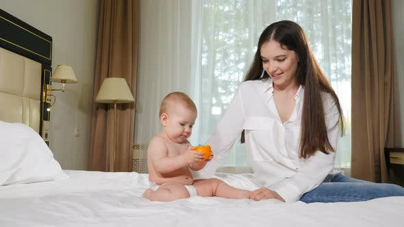 Happy Young Mother Looking at Her Baby Sitting on Bed. Concept of Children, Baby, Parenthood
