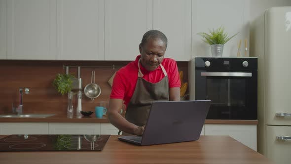 Thumbnail for Retired African Male Networking on Laptop in Kitchen