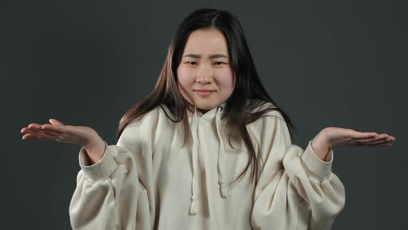 Thumbnail for Asian Unsure Girl in White Hoodie Shrugs Her Arms, Makes Gesture of I Don't Know