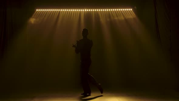 Thumbnail for Ballroom Dancer Guy Moves Gracefully on Stage. Dark Silhouette in Soft Yellow Lighting. Slow Motion.