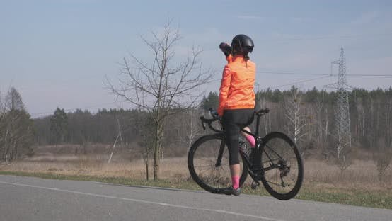 Thumbnail for Woman is drinking water and preparing for ride on bike. Woman on bicycle. Woman cycling concept