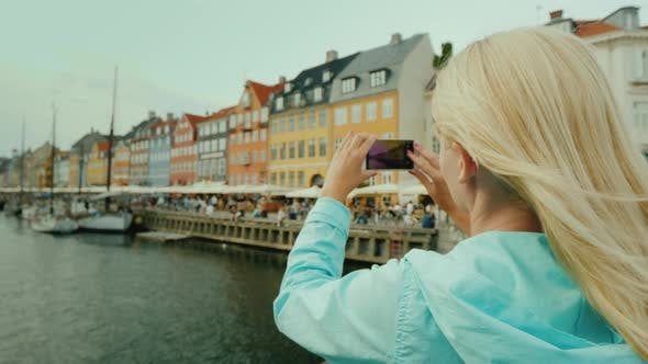 Cover Image for The Tourist Photographs the Famous Houses on the Nyhavn Canal. Tourism in Denmark Concept