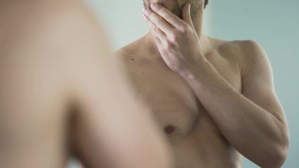 Thumbnail for Naked Middle-Aged Man Looking in Mirror, Touching His Beard Before Shaving