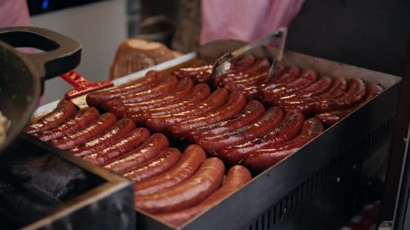 Thumbnail for Fresh Sausage and Hot Dogs Grilling Outdoors on a Gas Barbecue Grill.