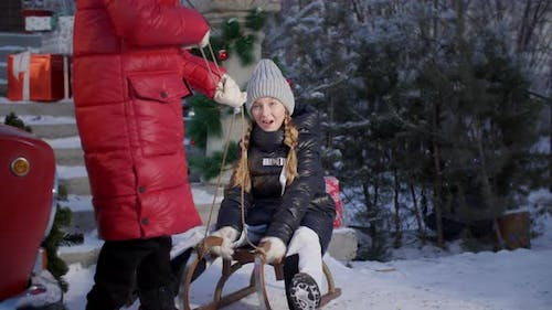 Playful Girl Sledding with Friend on Winter Holidays