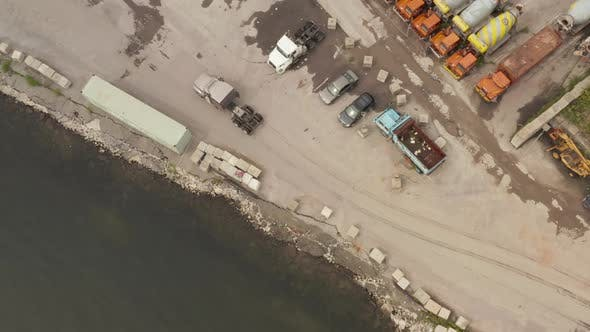 Thumbnail for AERIAL: Following Grey Cargo Truck in Docks of New York City Cloudy Grey Day