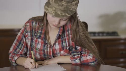Young Girl Sit at Home on the Table and Writing a Letter in Soldiers Cap