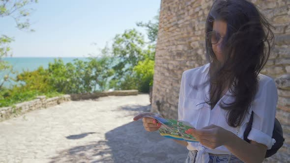 Thumbnail for Tourist Traveller Woman Walking in Ancient Building at the Sea Coast and Holding Tourist Map