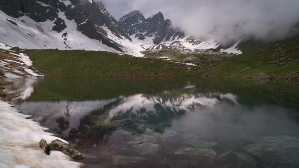 Thumbnail for Timelapse of a Clear Lake Surrounded By Mountains. Clouds Are Billowing