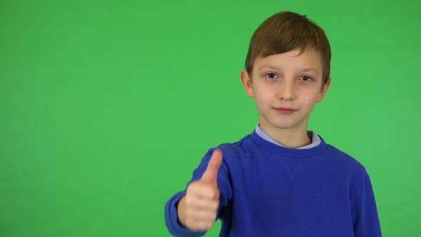 Thumbnail for A Young Cute Boy Smiles and Shows a Thumb Up To the Camera - Green Screen Studio