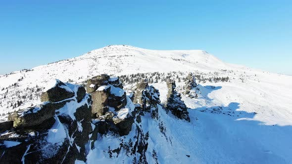 Spectacular Drone Flight Along Snow Covered Rock Peaks on a Sunny Winter Day