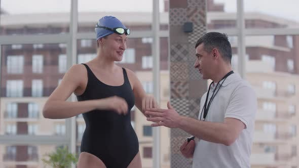 Female Swimmer Talking to Coach during Practice