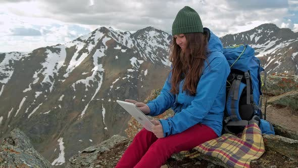 Thumbnail for Girl Hiker with a Tablet Sitting on a Rock on a Background of Mountains and Lakes, Norway