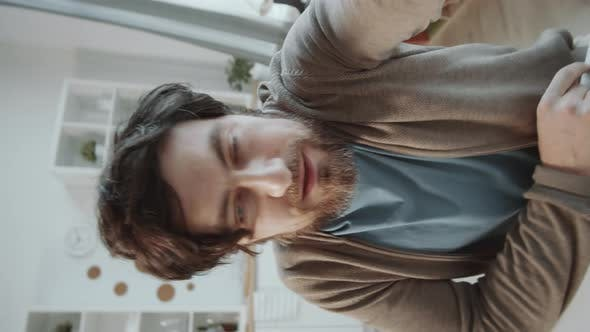 Thumbnail for Vertical Shot of Caucasian Man Talking on Video Call on Smartphone at Home