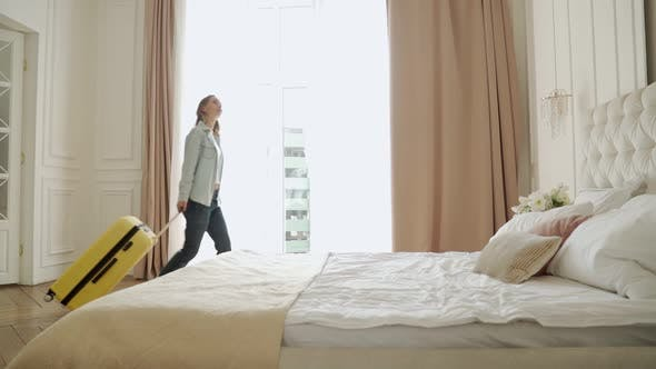 Woman Walking Into a Hotel Room with Suitcase and Fell on Bed Tired