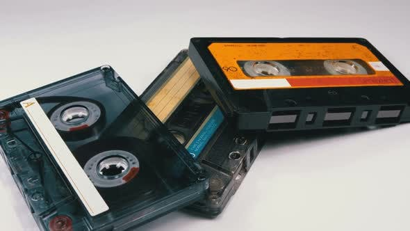 Thumbnail for Three Vintage Audio Cassettes Rotate on White Background