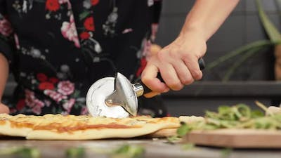 Cutting pizza with round cutter knife