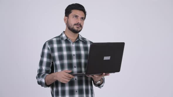 Thumbnail for Portrait of Young Happy Bearded Indian Man Thinking While Using Laptop