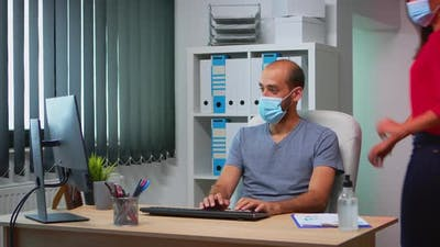 Coworkers with Face Masks Working