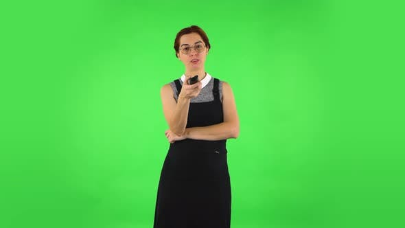 Thumbnail for Funny Girl in Round Glasses with TV Remote in Her Hand, Switching on TV. Green Screen