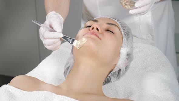 Anti-Aging Gesichtsbehandlung mit Golden Mask Cream Massage auf weiblichem Gesicht. Goldflocken hat Kollagen