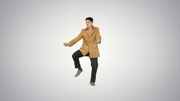 Thumbnail for Young man wearing trench coat dancing and having fun on